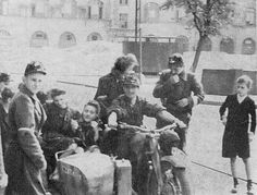 "Soldiers from Battalion ""Czata 49"" with a captured motorcycle. In the back courier Anna Wyganowska ""Ewa"" talking with ""Kropka""."