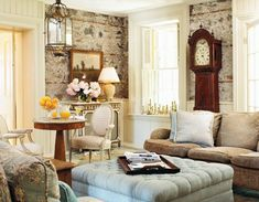 Isn't this vintage-style room dreamy? A recovered 19th-century English sofa and a pale blue tufted ottoman create a feminine, cosy space. An 1835 mahogany grandfather clock, 18th-century English bronze lantern and exposed stone walls offer old world charm.