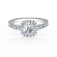 This timeless classic is a halo engagement ring from the Carmella collection. It features 1/6 ctw of diamonds. The signature handcrafted details include scroll hand engravings, milgrain edging and filigree. The center 0.75 carat round stone (shown) is a customized option.