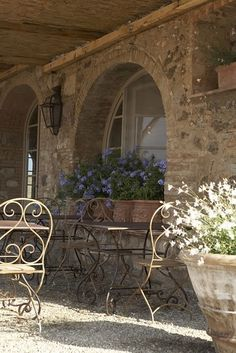 beautiful in stone, love the iron bistro chairs and potted flowers