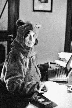 Image may contain: people sitting and indoor [Susan Sontag writing in bear costume, by Annie Leibovitz
