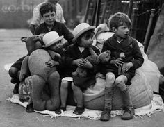 Children with their rescued toys, after their North London tenement homes were bombed during the night. London, 1940.