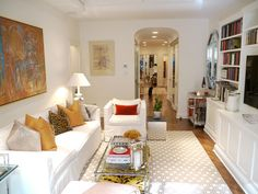 TV room ~ Love the color balance of artwork, pillows and hardwoods in this white room.