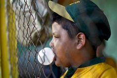 "A boy chews gum during a baseball practice at the ""23 de Enero"" neighborhood in Caracas March 2, 2011. Boys as young as five years old are training in Venezuela's Little Leagues. Some of them live in the city's slums or poorer neighborhoods and think baseball could be a ticket to a different life.  REUTERS/Jorge Silva"