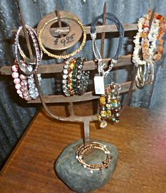 Bracelet display made from an old pitch fork and rock.