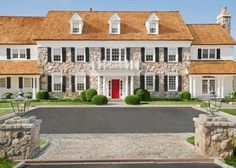 A traditional exterior with stone front, columns, black shutters and a red door!