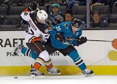 San Jose Sharks forward Logan Couture battles Chris Wagner of the Anaheim Ducks for a loose puck (Sept. 26, 2015).