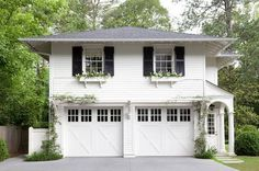 Gorgeous home exterior boasts a traditional two car garage framed by white siding and positioned under an above-garage apartment with two windows flanked by black shutters and fitted with white flower boxes. Above Garage Apartment, Garage Apartment Plans, Garage Apartments, Garage Apartment Interior, Apartment Door, White Apartment, Black Garage Doors, Carriage Garage Doors, Carriage House Plans