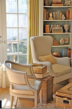 off white slip covers; blue paint inside shelf; low chair with interesting upholstary