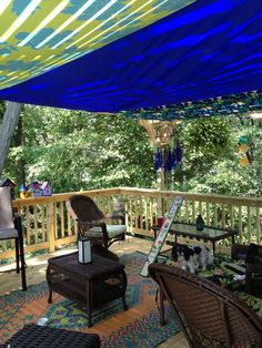 Second story deck with pergola, which is covered by several sails to keep it cool. A garden totem is in progress and a blue bottle chandelier made with copper wire hangs in the corner.