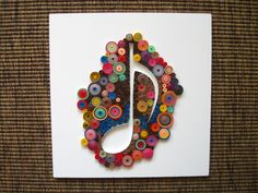 Quilled musical note on a white panel (the panel is 16.5x16.5 cm)