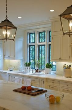 twin polished nickel, bridge faucets, side-by-side sinks, white kitchen cabinets, marble countertops, iron kitchen island lanterns