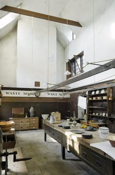 The Old Kitchen at Belton House, Lincolnshire, UK, showing an early nineteenth century compilation of the wooden table, scales, shelves and utensils