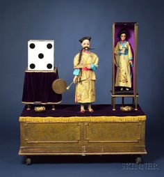 """Rare Henry Phalibois Automaton of a Chinese Magician and Vanishing Assistant, c. 1920, the magician with papier-mache head, articulated eyelids and in-active jaw, black mohair queue and moustache, standing between a silk-covered magician's cabinet and a large painted die on stand, a fan in his right hand and gong-hammer in his left, on paneled base painted to resemble marble, the electric motor driving three pulleys and thirteen boxwood cams, in Chinese robes and hat, magician 30"""", standing…"""