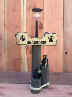 Solar Light Designs are handcrafted from landscaping timber for weather durability and includes a custom-painted sign, solar light and bear figurines.