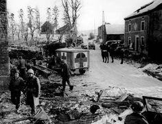 Jeeps, Dodge WC54 3/4-ton field ambulances, and US troops on a street in the heavily damaged town of Foy, close to Bastogne Belgium, 16 Jan 1945