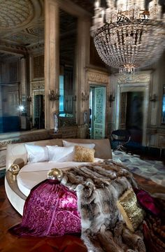 This room is gorgeous... chandeliers and a pop of color on the round bed...