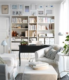 pretty space! bookshelves, gallery wall, white slipcovers, little bits of blue