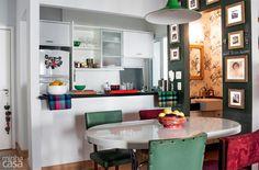 Sala de estar integrada com a cozinha, criando um ambiente vintage, moderno com antigo. A parede no tom verde musgo lembra um ambiente boêmio/antigo.