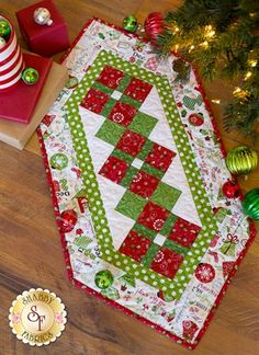 Jingle All The Way White Table Runner Kit: Add an extra festive flair to your table this Christmas with the Jingle All The Way Table Runner! This fun holiday table runner features basic piecing but will wow your guests with its complex look. Table Runner finishes to 17