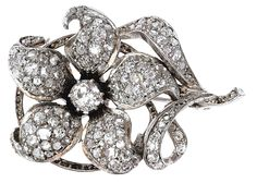 Antique diamond brooch    End 19th cent. 18 ct. gold with silver, ca. 12 g, flower with 1 old-cut diamond and rose diamonds, total c. 1,20 ct L.P. Verso brooch setting add. 40 x 26 mm, weight c. 12 g.