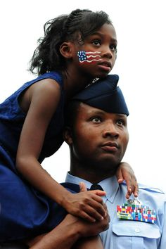 Air Force Tech Sgt. Marquis Mullins and his daughter Anya listen as President Barack Obama delivers remarks at an Independence Day barbeque.