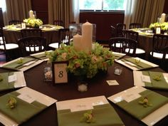 Assorted pillar candles accented with lush green blooms featured in wood box.