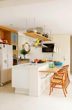 Os arquitetos, optaram por uma bancada colada na ilha central. A mesa serve de apoio para refeições rápidas e para quem assiste ao preparo dos pratos. Mesa e armários foram revestidos de laminado.    Outra boa solução é a prateleira suspensa. Encaixada na coifa e presa ao teto por cabos metálicos, ela suporta panelas e objetos de decoração.