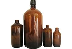 Set of four dark amber apothecary bottles. One has original cap, three others have been lost.