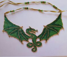 This dragon is completely hand beaded using only beads and thread. The beads are very shiney so the pictures are not exact. The gold beads are 22K plated. The wing span is 9. The strap is a gold ribbon with gold tone pewter beads and glass rounds! It ties with a bow in the back. Hang it low or high as a choker. It almost looks like a shiny tattoo! It is an elegant one of a kind piece that you will love to show off!   The pattern is from Sarahs Beading Obsession
