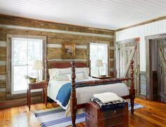 The rustic bedroom in this cabin is so cozy! The handsome cannonball bed is one of the few new pieces in the home. Layers of white bedding keep the mahogany item from feeling heavy, while a pretty pastoral scene in its original gold frame and marble bedside lamps dress up the room without adding a lot of fuss.