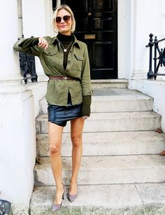 Pandora Sykes of Pandora Sykes in a sexy leather mini skirt and army green top.