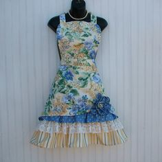 This is my Petticoat Ruffle Style Apron which has been featured on FOOD NETWORKS Cake Wars. With its ruffles and lace it is so fun to wear. The floral print is a heavier cotton for long wear and is done in yellow, periwinkle blue and green. The pull-up with the flower shows off the rows