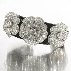 A rare art deco black lacquer bangle with diamond flowers set in platinum, by Cartier, circa 1935
