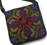 The bag is knit, and the colorful raised additions are crochet