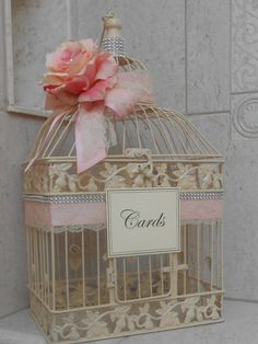 This beautiful large ivory birdcage would be the perfect addition to any gift table. Cage has been adorned with light pink satin ribbons with an