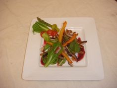 Green salad with diced rabbit. raspberry dressing and a touch of rosted pumpkin seeds. Dry carrots as decor