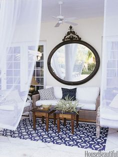 "This mirror makes the porch of a Florida home by designers Courtney Coleman and Bill Brockschmidt feel more like an actual room. An added benefit? ""At night it reflects the candlelight so beautifully,"" Coleman says. Smith & Hawken sofa;"