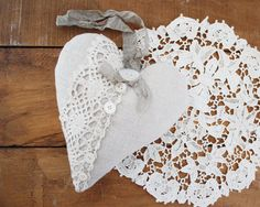 This heart is made with linen in a grey/taupe color. Its embellished with a bit of vintage lace and a row of tiny vintage buttons with one large button at the top. A length of crinkled grey seam binding makes a hanging loop. Its a perfect touch for doorknobs, bedposts, or drawer pulls!    The heart measures about 4 1/2 wide and tall. Its filled with fragrant dried lavender.    Do you like lavender hearts? See more of them here…