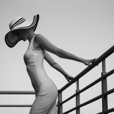 Фото Девушка в платье и в шляпе стоит держась за перила, фотограф Michał Magdziak