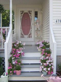 flower lined steps and screen door. love the stand with the birdhouses