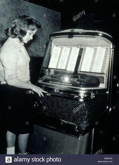 1950s TEENAGE GIRL SELECTING MUSIC ON COIN-OPERATED JUKEBOX Stock Photo
