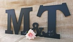 alternative guest book- painted wooden letter and people sign with a silver sharpie