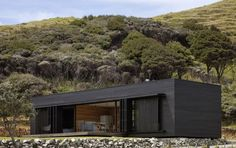 "roomonfire-good-design:  'Storm Cottage' by Fearon Hay. ""Located on the east coast of Great Barrier Island – a black rough sawn timber box sits looking north to the sea. The dark exterior palette is completed with a layer of perforated metal screens. This operable layer allows the moderation of light / air and protection both when occupied and alone.""  †"
