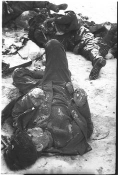 "A German KIA, still wearing his glasses and Iron Cross, 2nd Class, lies near a pile of dead comrades inside the Stalingrad ""Kessel"" (cauldron) and was photographed by a Red Army photographer after the end of the battle in Jan 1943."