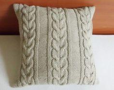 J'ai tricoté cette housse de coussin à l'aide d'une épaisse et douce grosse laine Ivoire avec un point de câble design sur le côté à l'avant et arrière ainsi. La housse du coussin se ferme sur le dos avec un style denveloppe et trois boutons au crochet. Ce coussin intemporel est sûr d'ajouter une touche d'élégance à votre maison. Il peut être un complément parfait à n'importe quelle pièce de couleur clair. Il ferait aussi un cadeau parfait !  Le cas se situerait un 18 x 18 (46 x 46 cm.)…