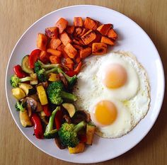 two pasture raised eggs with veggies sautéed in olive oil and roasted sweet potato