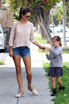 The supermodel shows off her famous legs in a pair of J Brand denim cutoffs, paired with a soft pink knit and matching flats.   - HarpersBAZAAR.com