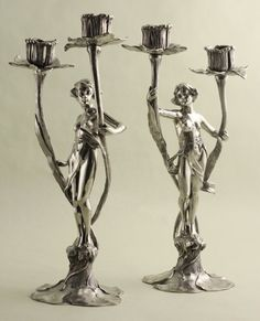 "Figural Art Nouveau Pewter Candelabra: Pair of fine figural Art Nouveau Candelabra. Polished pewter maidens representing Day and Night. One figure with eyes gazing forward while the companion gazes downward. Naturalistic lily pad bases support the whispy figures each grasping vine-like stems; candle cups rest at their top. Made by Argentor in Austria circa 1905. Firm's marks upon bases. Dimensions: 13"" H, 6 3/4 W"". Offered by Cherub Antiques Gallery: http://www.cherubantiquesgallery.com/"