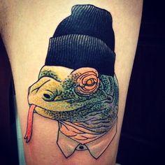 Kimodo Dragon in a watchman's cap tattoo by adrian edek